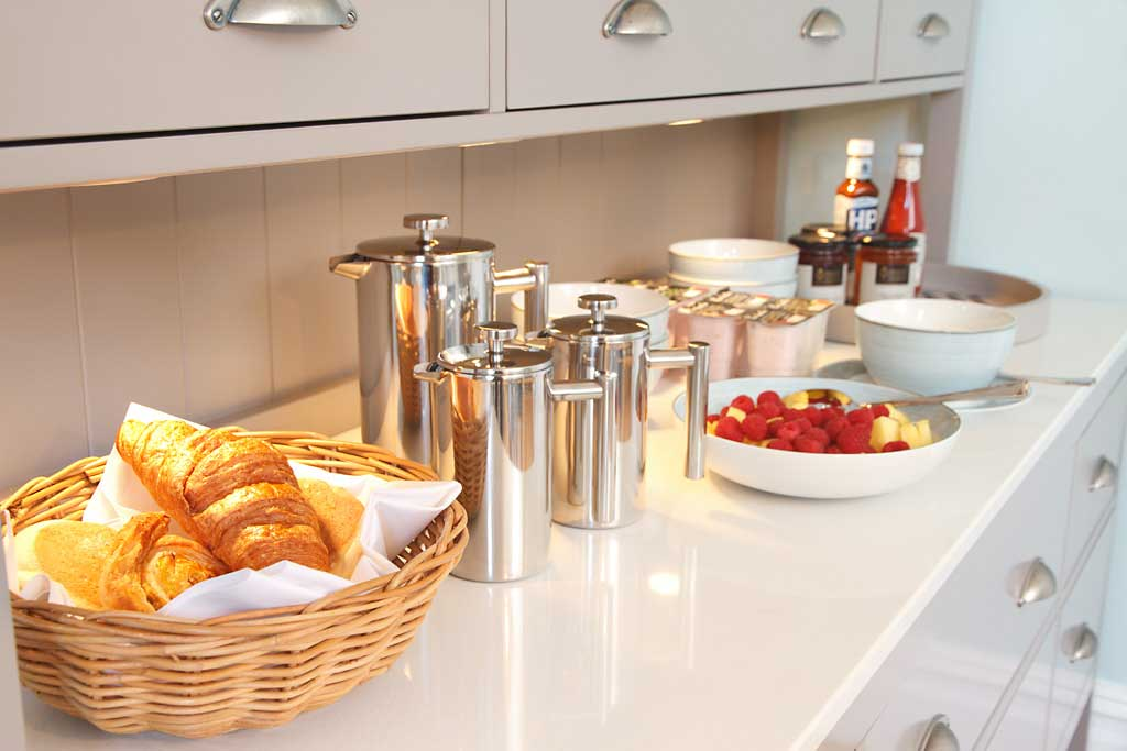 The sideboard in the breakfast room laid out with cereals and pastries